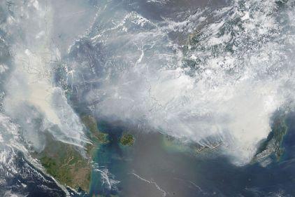 Foto tomada por la NASA el 24 Septiembre de 2015. Los incendios asociados al cultivo de palma aceitera llenaron de humo el cielo de la región. A la izquierda se puede apreciar el sur de Sumatra, a la derecha (apenas de ve) estaría el oeste  de Borneo.